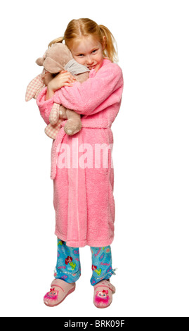 Little, small, young,caucasian girl in her pyjamas, slippers and dressing gown  ready for bed cuddling her toy - Stock Photo