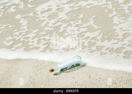Message in a bottle washed up on shore - Stock Photo