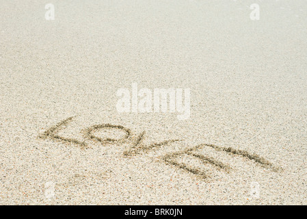 The word 'love' written in sand at the beach - Stock Photo