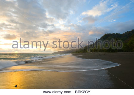 The tide rises at sunset on a remote beach in Costa Rica - Stock Photo