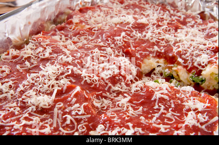 several rows of fresh manicotti stuffed with peppers, chicken and cheese in a pan ready to cook - Stock Photo