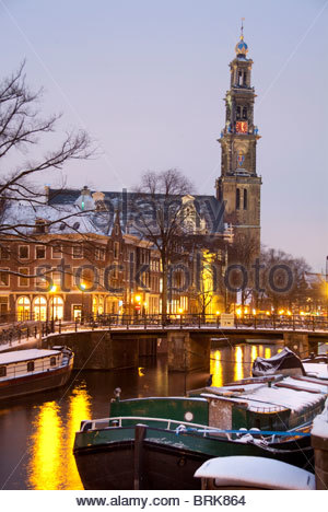 Canals at Christmas in snow with Wetserkerk tower in background. - Stock Photo