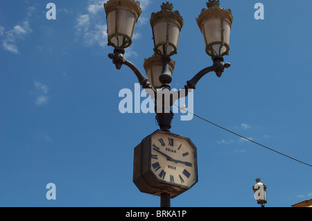 French street clock with lamp posts attached in Nice - Stock Photo