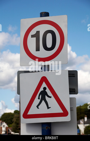 10 mph speed limit sign and pedestrians walking sign - Stock Photo
