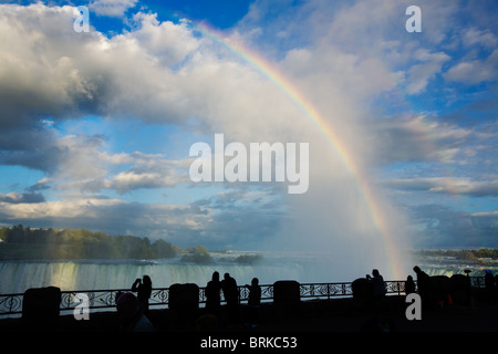 Tourists gawk at rainbow and spectacular clouds over Horseshoe Falls, Niagara Falls, Ontario, Canada - Stock Photo
