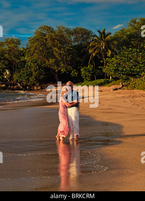 senior couple walking on a maui beach at sunset - Stock Photo