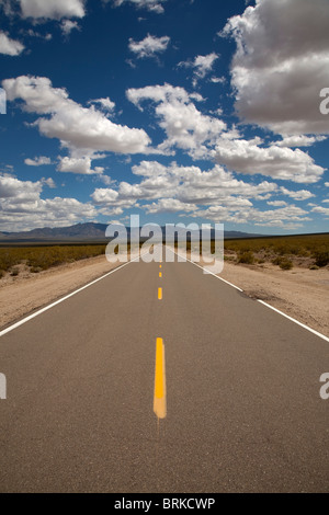long deserted road in the Mojave Desert in California USA with mountains in the distance and fluffy white clouds - Stock Photo