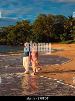 senior couple walking on a maui beach at sunset - Stock Photo