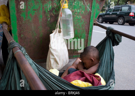 A young boy is sleeping in a hammock tied to a Cintri garbage collection cart on Norodom Boulevard in Phnom Penh, - Stock Photo