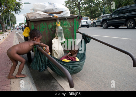 Two young boys living in poverty relax on a Cintri Garbage Company trash cart on Norodom Boulevard in Phnom Penh, - Stock Photo