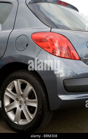 Close up view of rear light and plastic bumper on a peugeot car. - Stock Photo