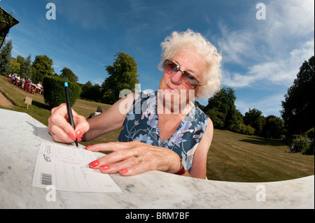 Elderly woman sitting outdoors writing a postcard on a hot summers day. - Stock Photo