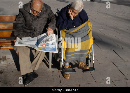 Spain Barcelona, old senior couple sitting on bench in the sun, reading newspaper and sleeping - Stock Photo