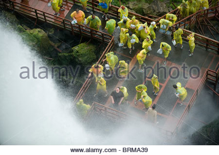 Tourists standing in the mist from Niagra Falls in New York. - Stock Photo