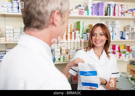 Pharmacist handing over prescription - Stock Photo