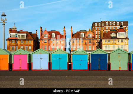 Colourful beach huts and buildings along the promenade of Hove seafront, Brighton & Hove, East Sussex, UK - Stock Photo