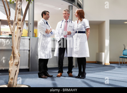 Doctors and nurse talking in surgery - Stock Photo