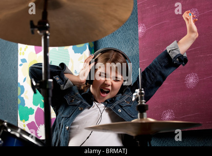 Girl listening to headphone with drums - Stock Photo