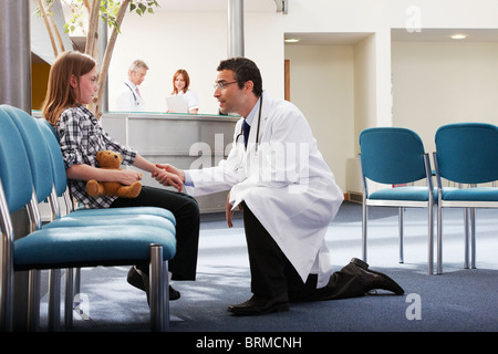 Doctor greeting young girl in surgery - Stock Photo