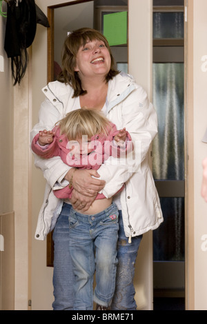 Working mother dropping off her toddler daughter at daycare facility who is refusing to attend day care facility. - Stock Photo