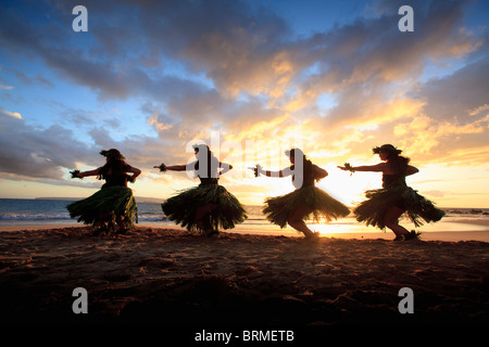 Silhouette of hula dancers at sunset at Palauea Beach, Maui, Hawaii. - Stock Photo
