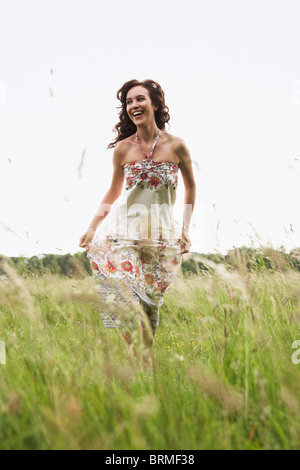Woman running through wild meadow - Stock Photo