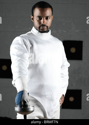 Portrait of a fencer wearing fencing uniform in a gym - Stock Photo