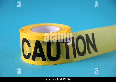 roll of CAUTION tape on blue surface - Stock Photo