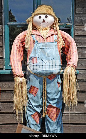 Scarecrow standing against a wooden shed wall