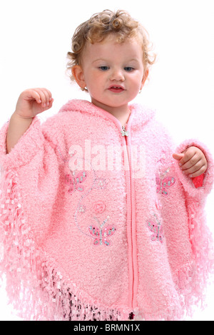 Lovely baby girl walking in pink poncho looking like an angel isolated on white - Stock Photo