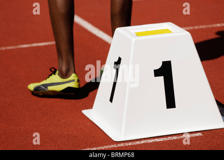 legs of a male sprinter next to starting block number one on athletic track outside - Stock Photo