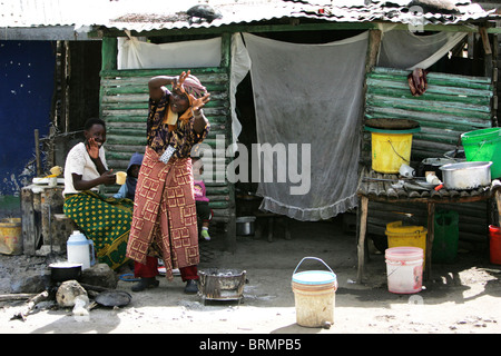 Two woman with two young children outside their makeshift dwelling - Stock Photo