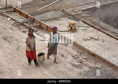 Two female construction workers carrying wet cement in a bucket carried on a pole between them - Stock Photo