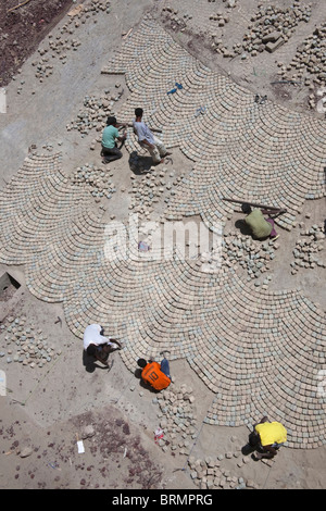Overhead view of workers laying a cobble stone pavement in a technique learnt during Colonial times from Italian - Stock Photo