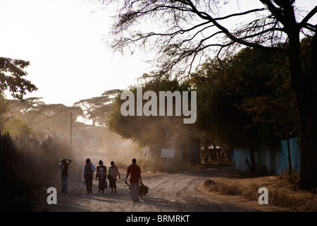 Local people walking to work on a dusty road in Awassa - Stock Photo