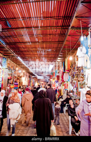 Local people shopping in one of the many narrow streets that make up the Marrakesh souk or market - Stock Photo
