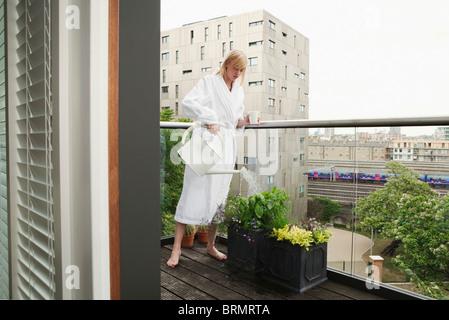 Woman watering flowers on balcony - Stock Photo
