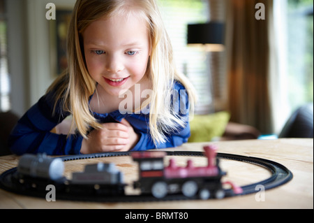 Girl playing with toy train - Stock Photo