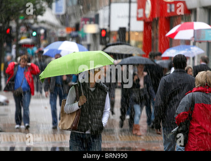 Shoppers on a cold and rainy day. - Stock Photo