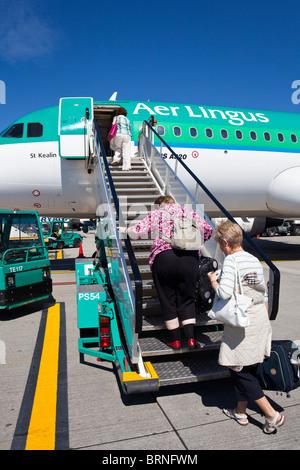 passengers boarding RyanAir  Aer Lingus flight, Dublin airport, Ireland - Stock Photo