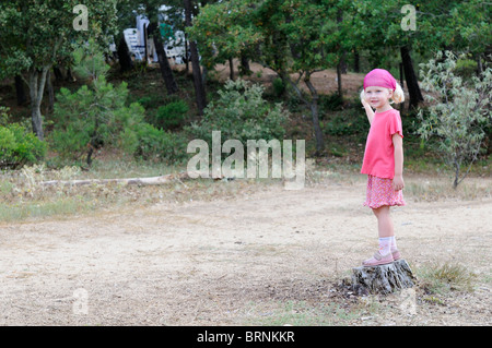 Stock photo of a four year old girl standing on a tree stump. - Stock Photo