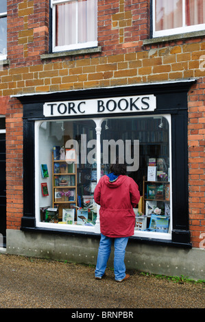 A woman looking in the window of Torc Books, a small secondhand bookshop in the village of Snettisham, Norfolk - Stock Photo