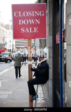 Man with closing down sale placard on street in London during one of th UK's worst recessions. Photo:Jeff Gilbert - Stock Photo