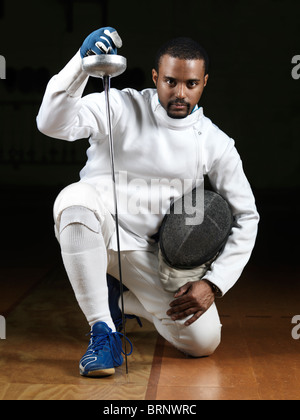 Portrait of a fencer wearing fencing uniform and holding an epee in a gym on black background - Stock Photo