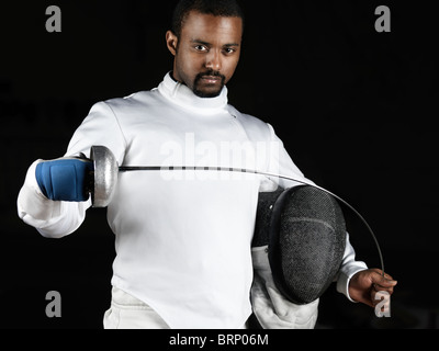 Portrait of a fencer wearing fencing uniform bending an epee in his hands. Isolated on black background - Stock Photo