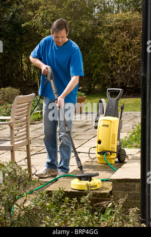 Man using a pressure washer to clean a patio - Stock Photo