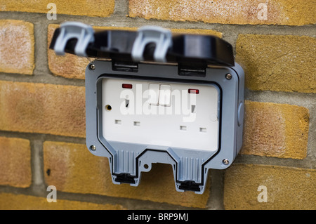 External mains power socket for UK mains electricity attached to a brick wall. - Stock Photo