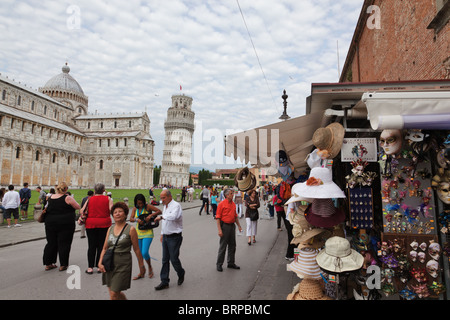 Tourists in Piazza del Duomo with Leaning tower of Pisa in background, Italy - Stock Photo