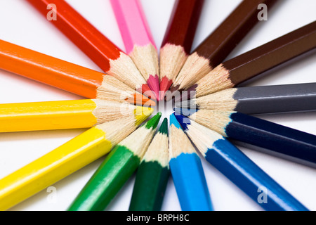 Close-up of a selection of colored pencil crayons, arranged like a color wheel. - Stock Photo
