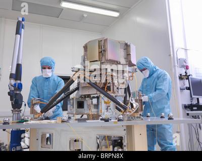 Workers assembling satellite dish - Stock Photo
